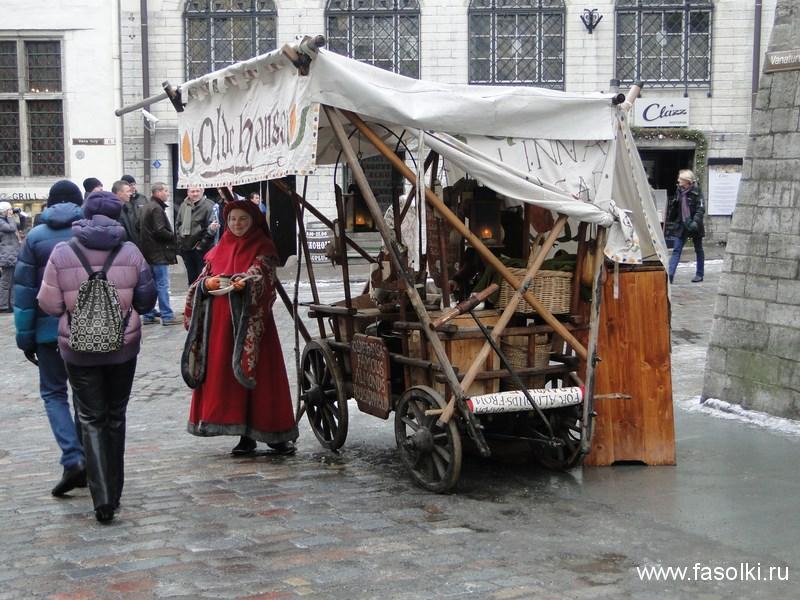 Продавщица миндаля в средневековых одеждах на Ратушной площади Таллина