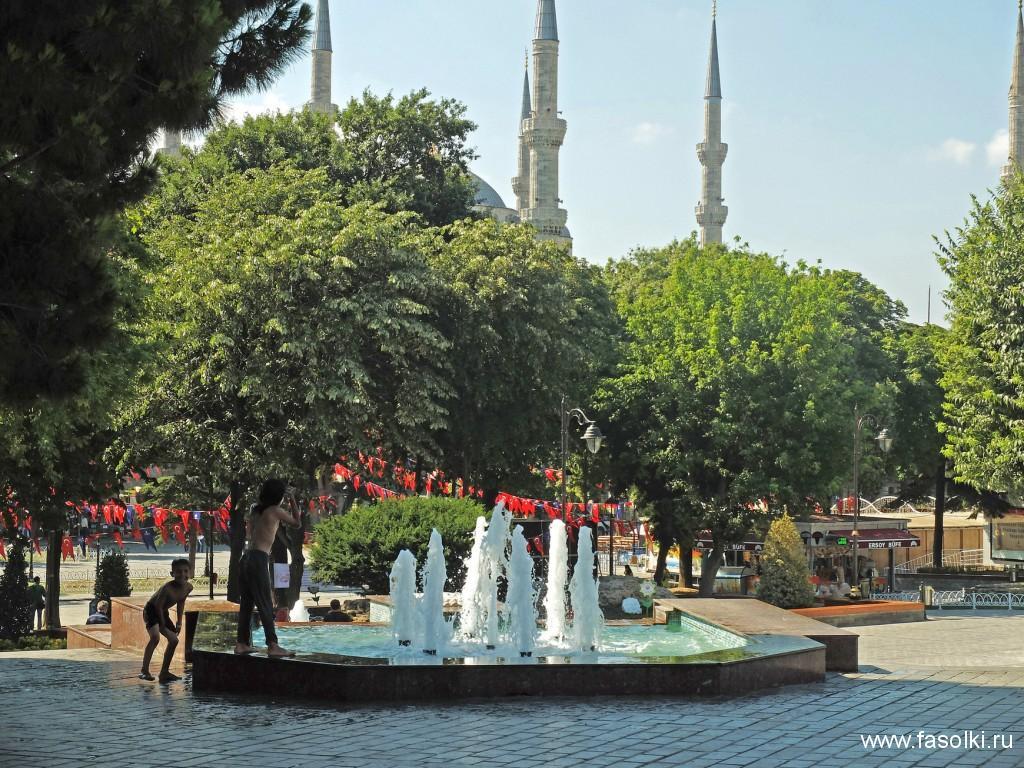 Дети купаются в фонтане. На заднем плане - Голубая мечеть